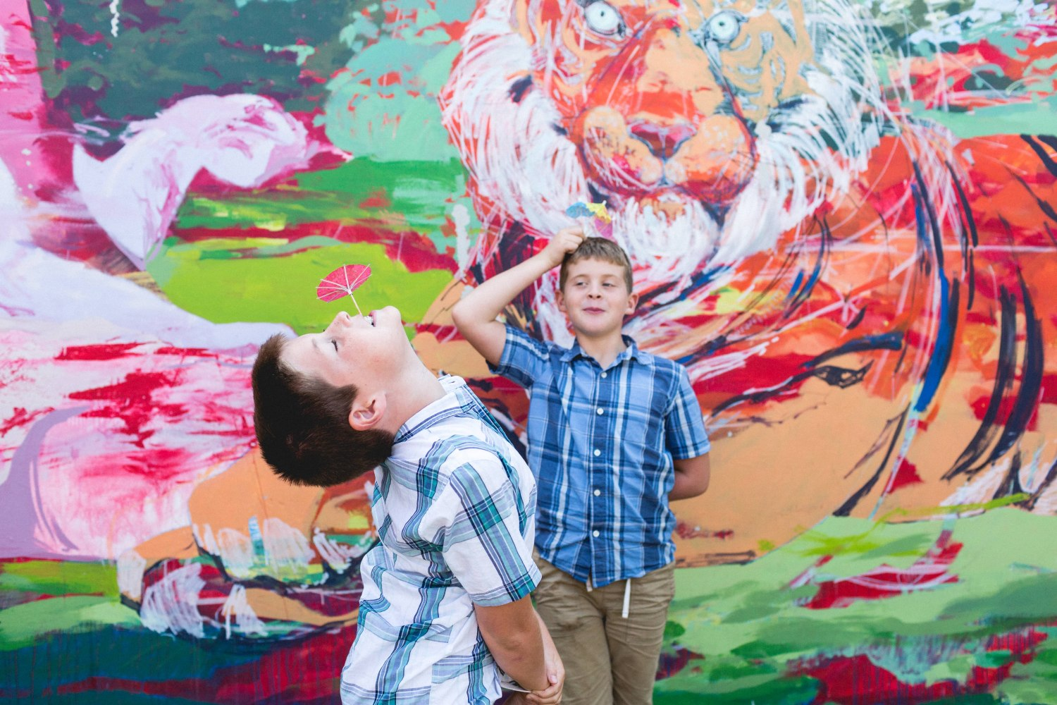 Brothers in front of a mural one with a paper umbrella in front of a mural Oakland