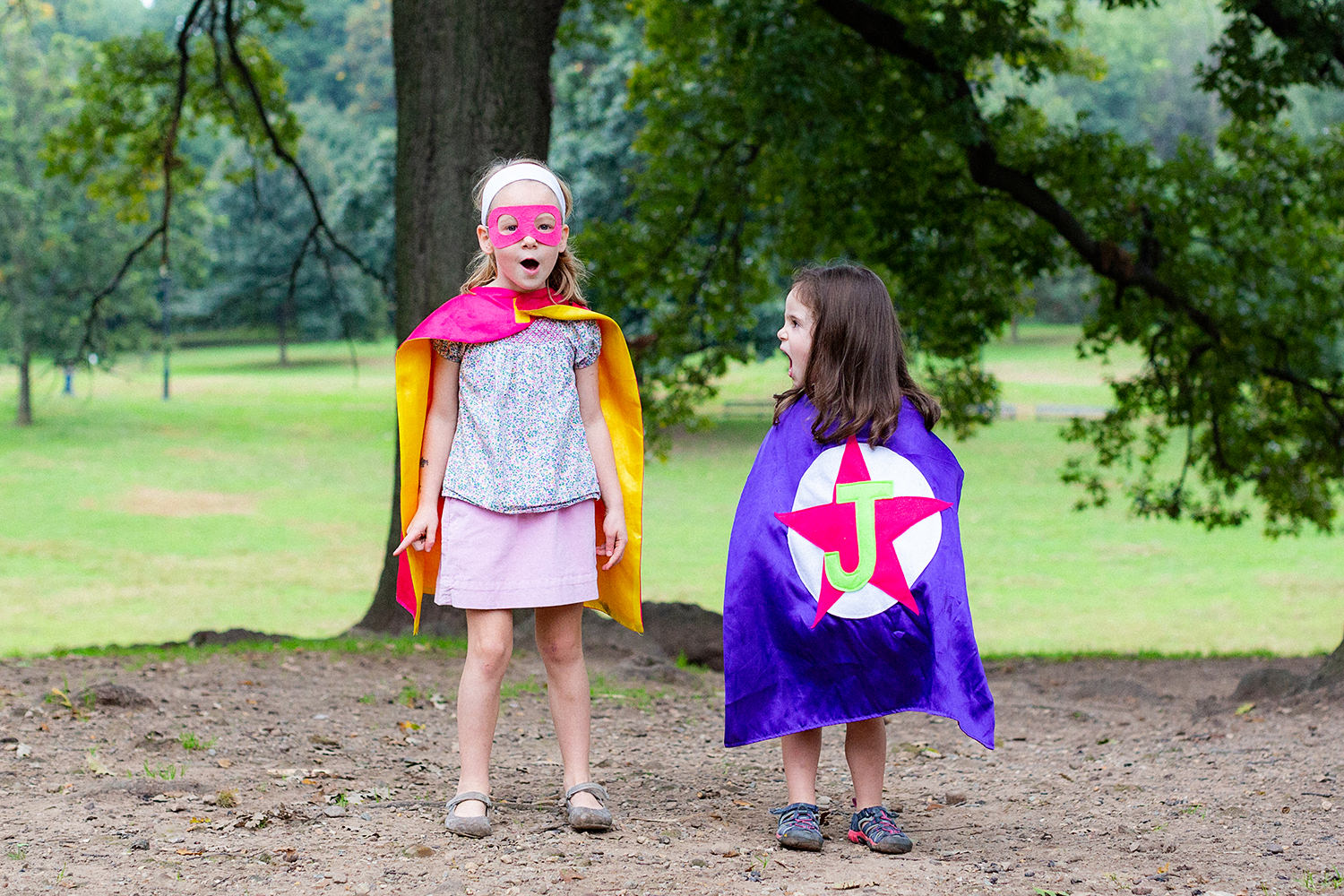 Sisters with capes and masks in Prospect Park